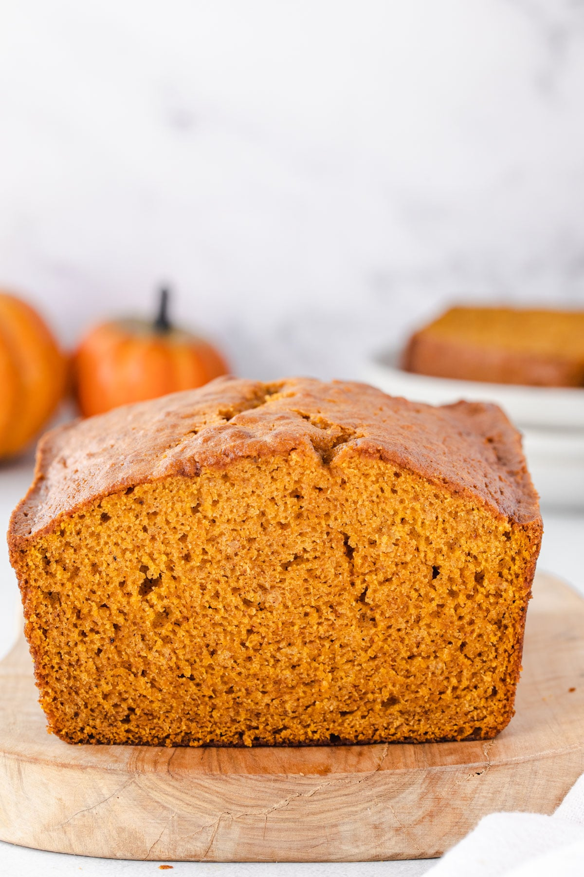 straight on view of a loaf of pumpkin bread with the first piece sliced off.