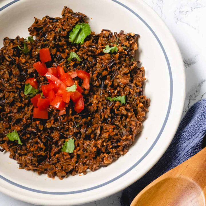 Bowl of Mexican wild rice topped with cilantro and chopped tomatoes, with a wooden spoon on the side.