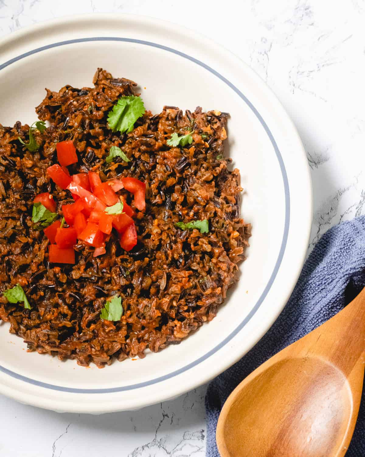 Wild rice in a white bowl. Garnished wtih tomatoes and cilantro. There is a wooden spoon on the side.