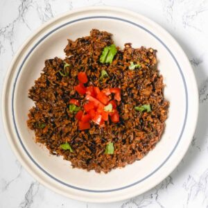 Bowl of Mexican wild rice, topped with chopped tomatoes and cilantro.
