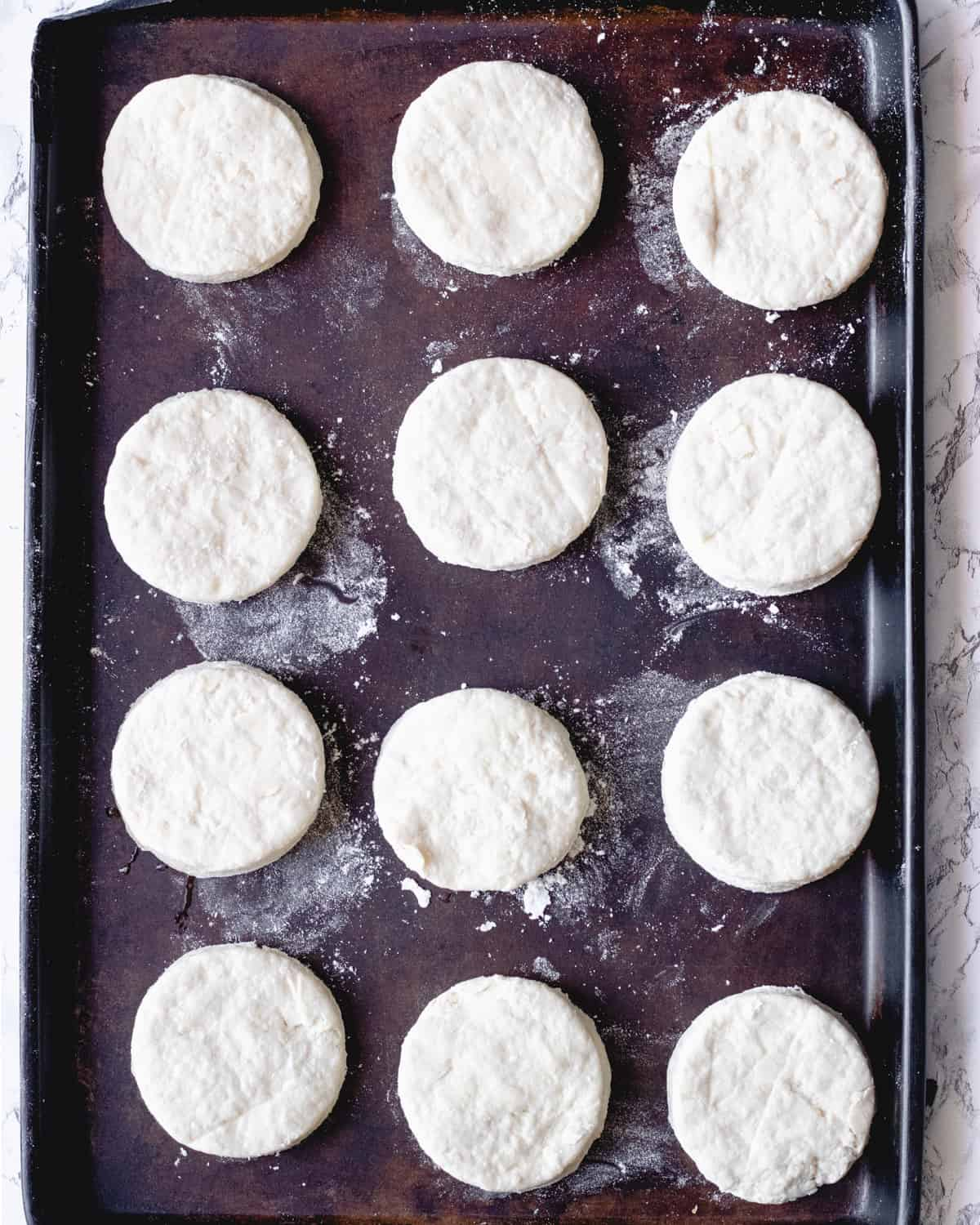 Baking sheet with 12 circles of biscuit dough laid out in 3 rows.