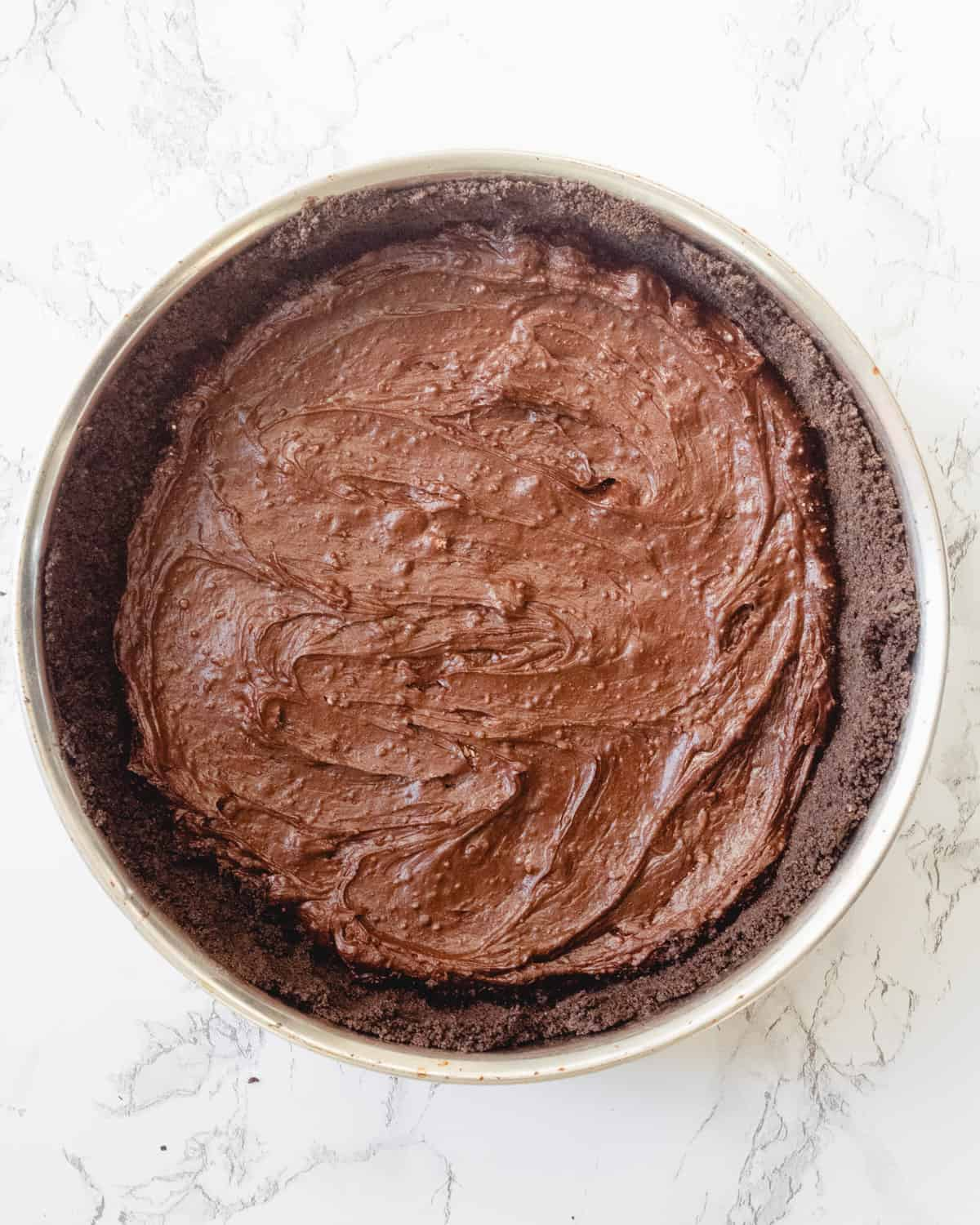 Flourless chocolate cake batter is spread over the Oreo crust.