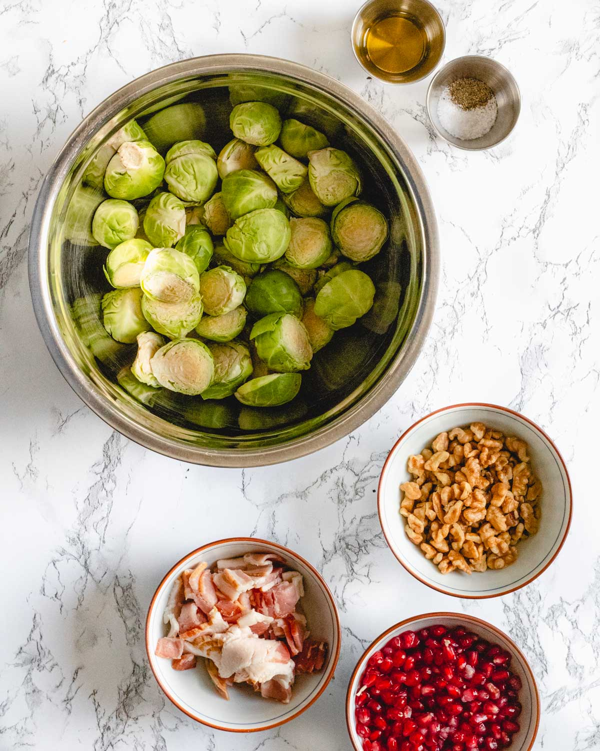 Brussels sprouts ingredients: Brussels, walnuts, bacon, pomegranates, oil, salt and pepper.