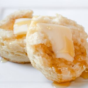 Buttermilk biscuit, sliced open with butter and honey.