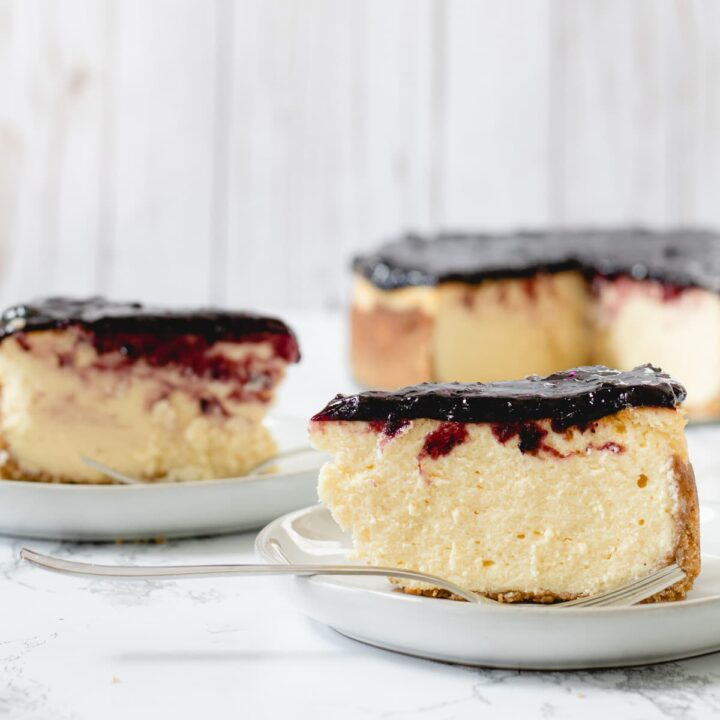 Two slices of huckleberry cheesecake with the whole cheesecake on the right.