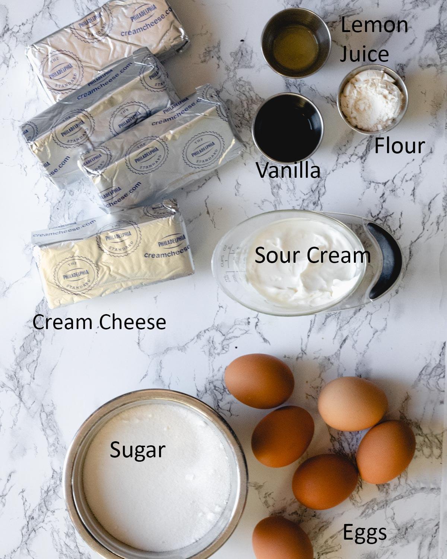 Cheesecake ingredients: Cream cheese, sugar, eggs, flour, vanilla, lemon juice, sour cream.