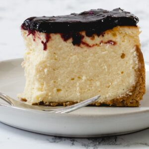 Slice of cheesecake on a plate with a bite out of it.