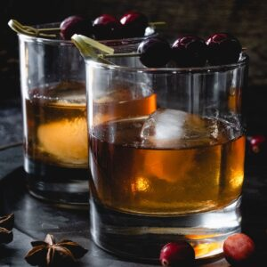 Two cranberry old fashioned cocktails.