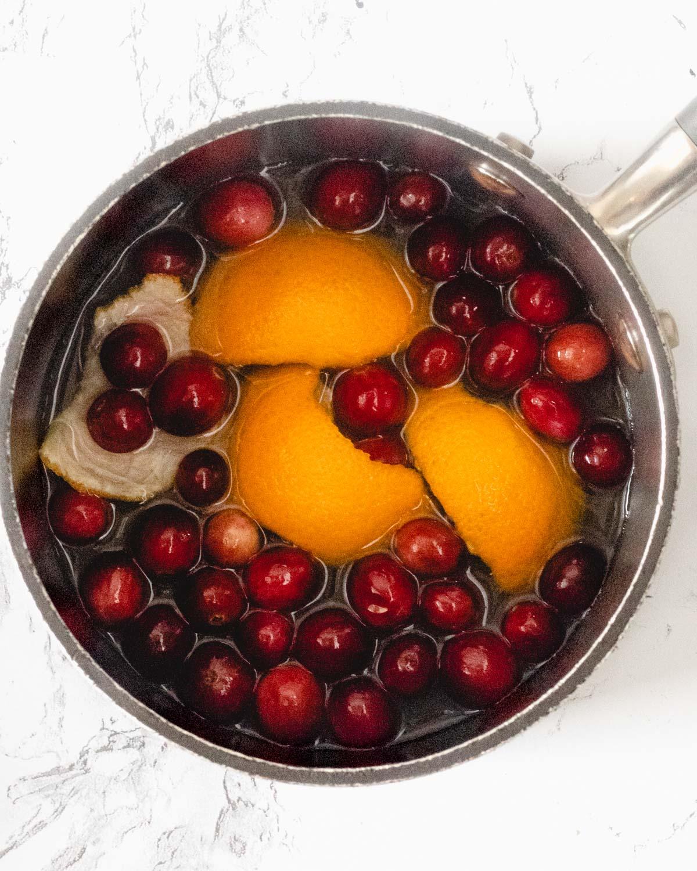 Saucepan with cranberries, orange peel, water, and granulated sugar.