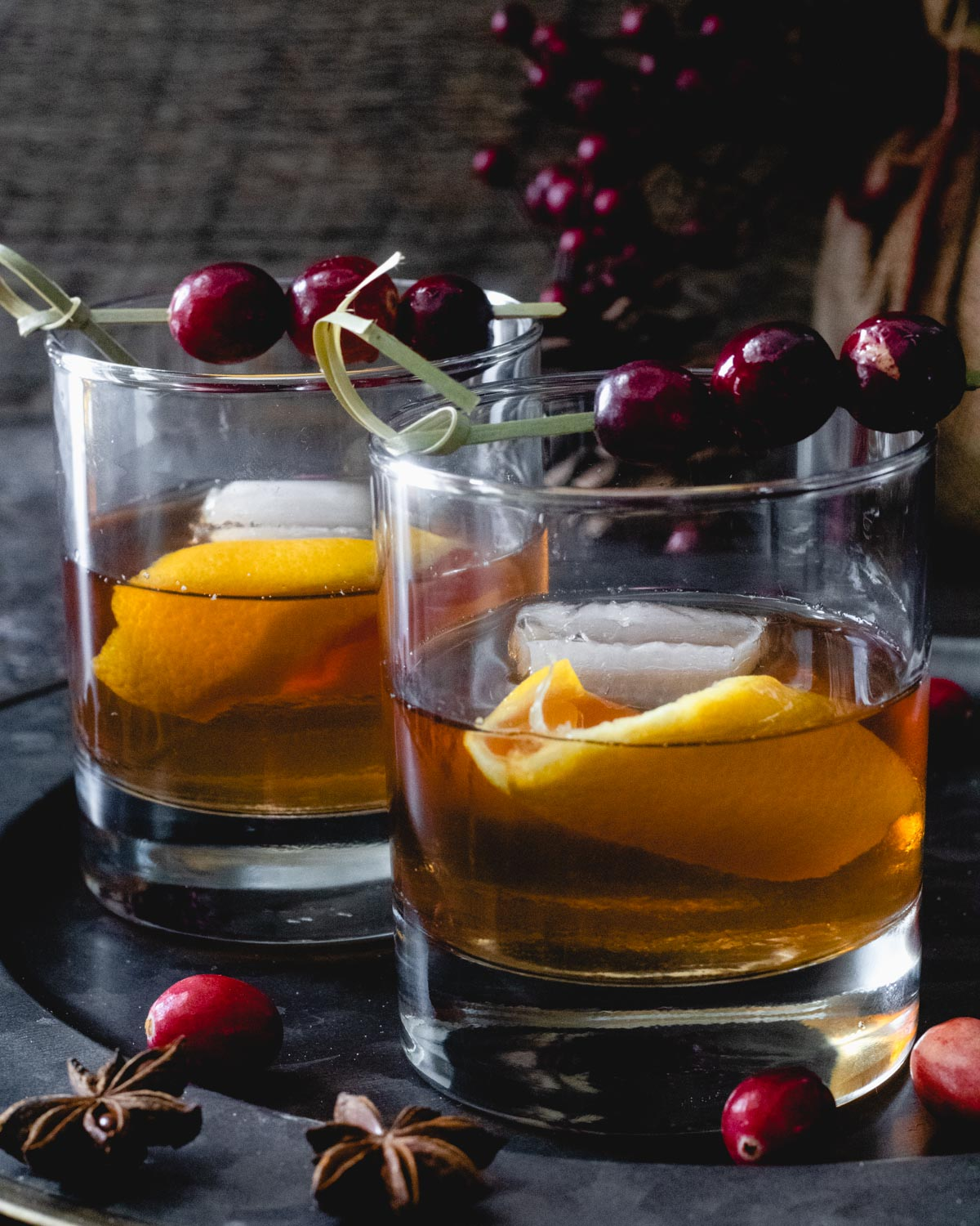 Two cranberry old fashioneds on a tray, with orange peel in glass and cocktail picks with cranberries.