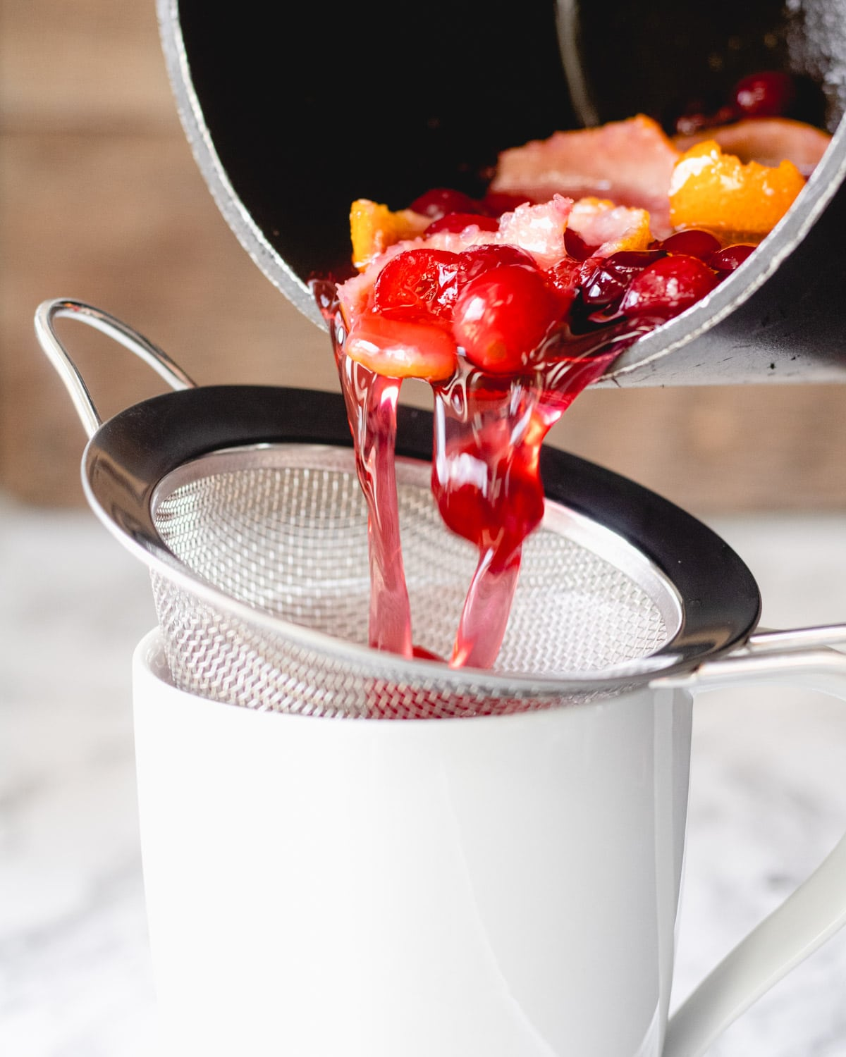Cranberry simple syrup being poured through a strainer into a mug.