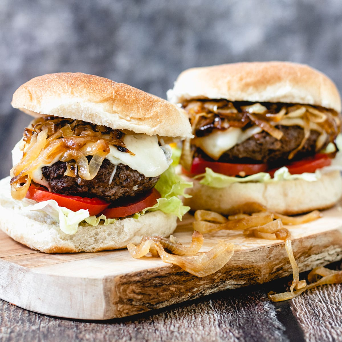 Two elk burgers on a wooden board.