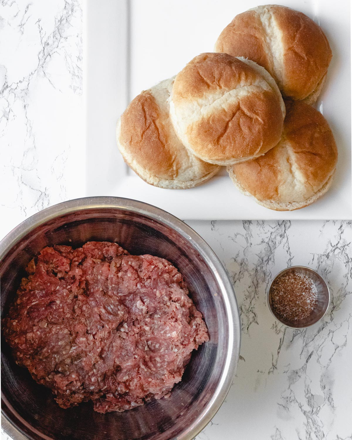 Bowl of ground meat with a ramekkin of seasoning and a plate with 4 buns.
