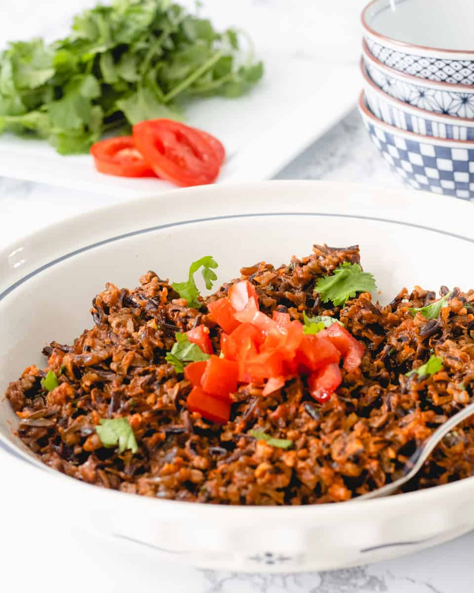 Bowl of Mexican rice with cilantro and tomato in the background.