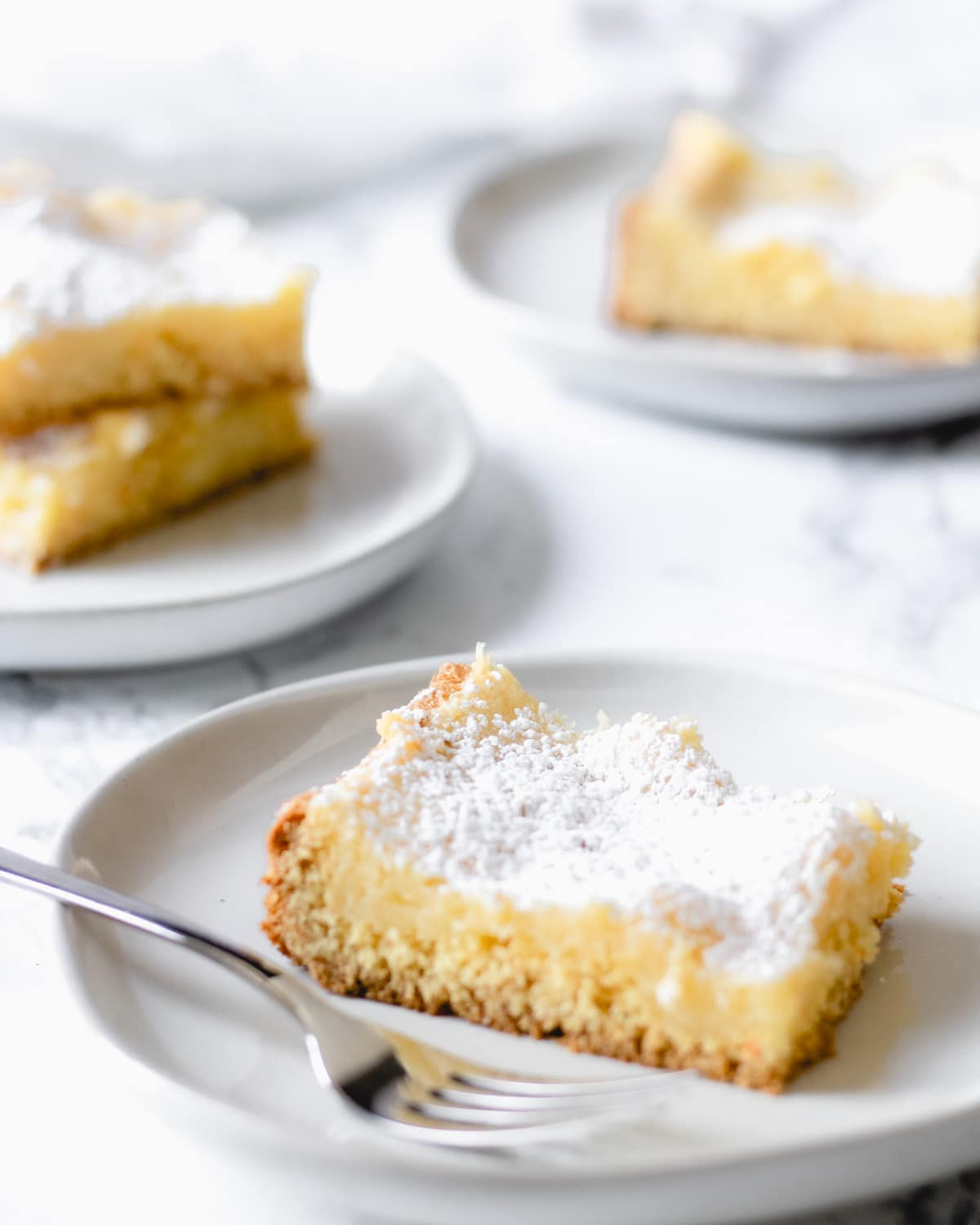 Square of gooey butter cake on a plate with a fork. Other plates have pieces stacked.