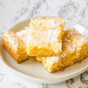 3 pieces of gooey butter cake stacked on a plate.