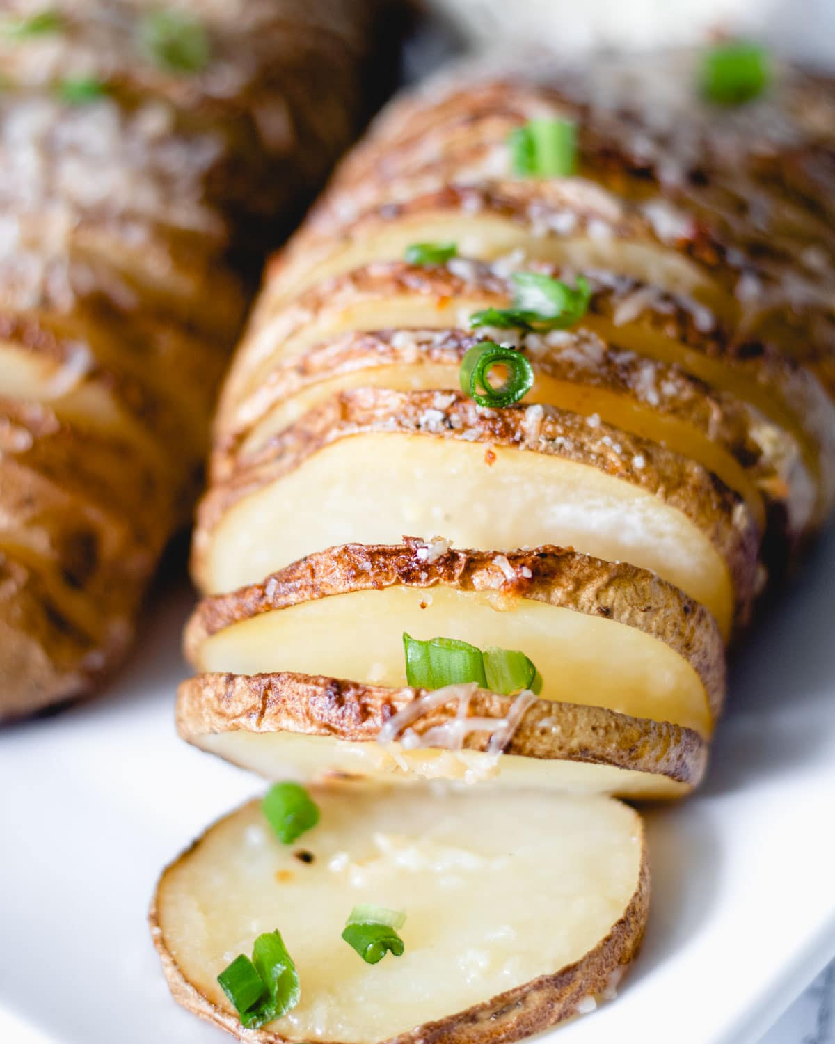Hasselback potatoes with garlic, Parmesan, and green onions.