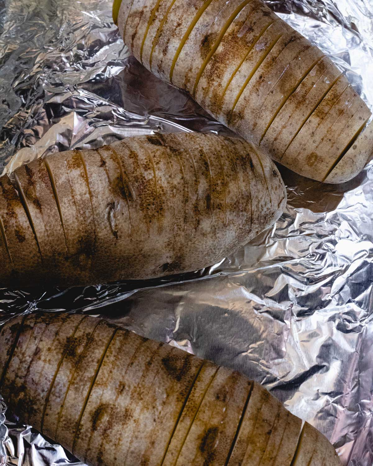 3 sliced potatoes in a foil-lined baking dish.