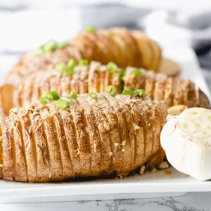 3 Hasselback ptoatoes on a platter with garlic.