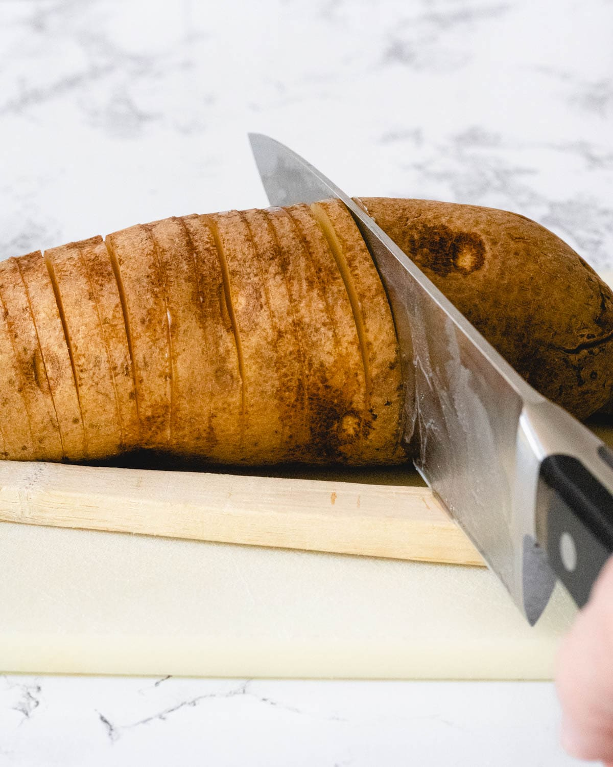 Slicing a potato in ¼-thick slices, using a spoon to stop the knife from cutting all the way through.