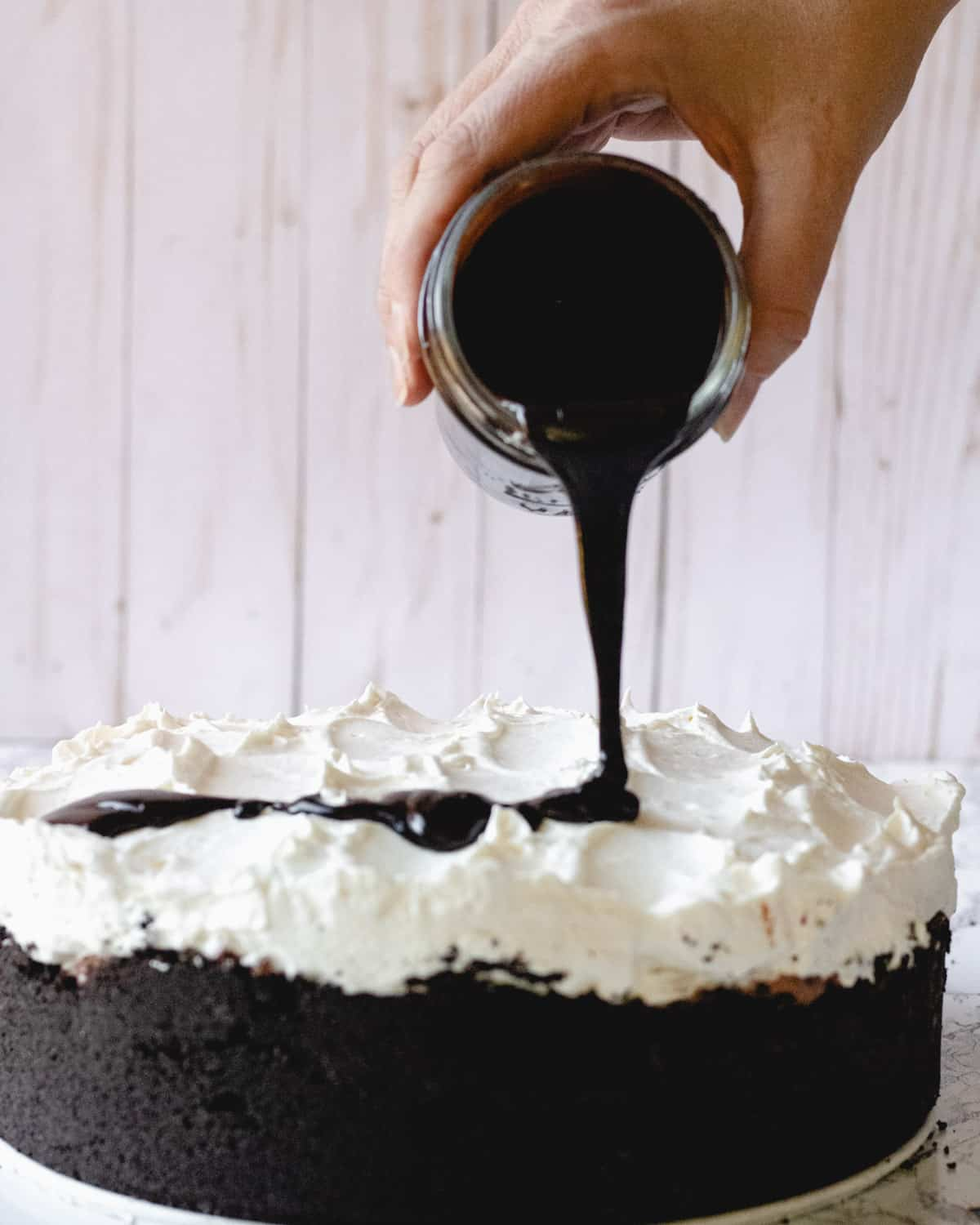 Mississippi Mud Pie with hot fudge being poured out of a jar over the top of the pie.