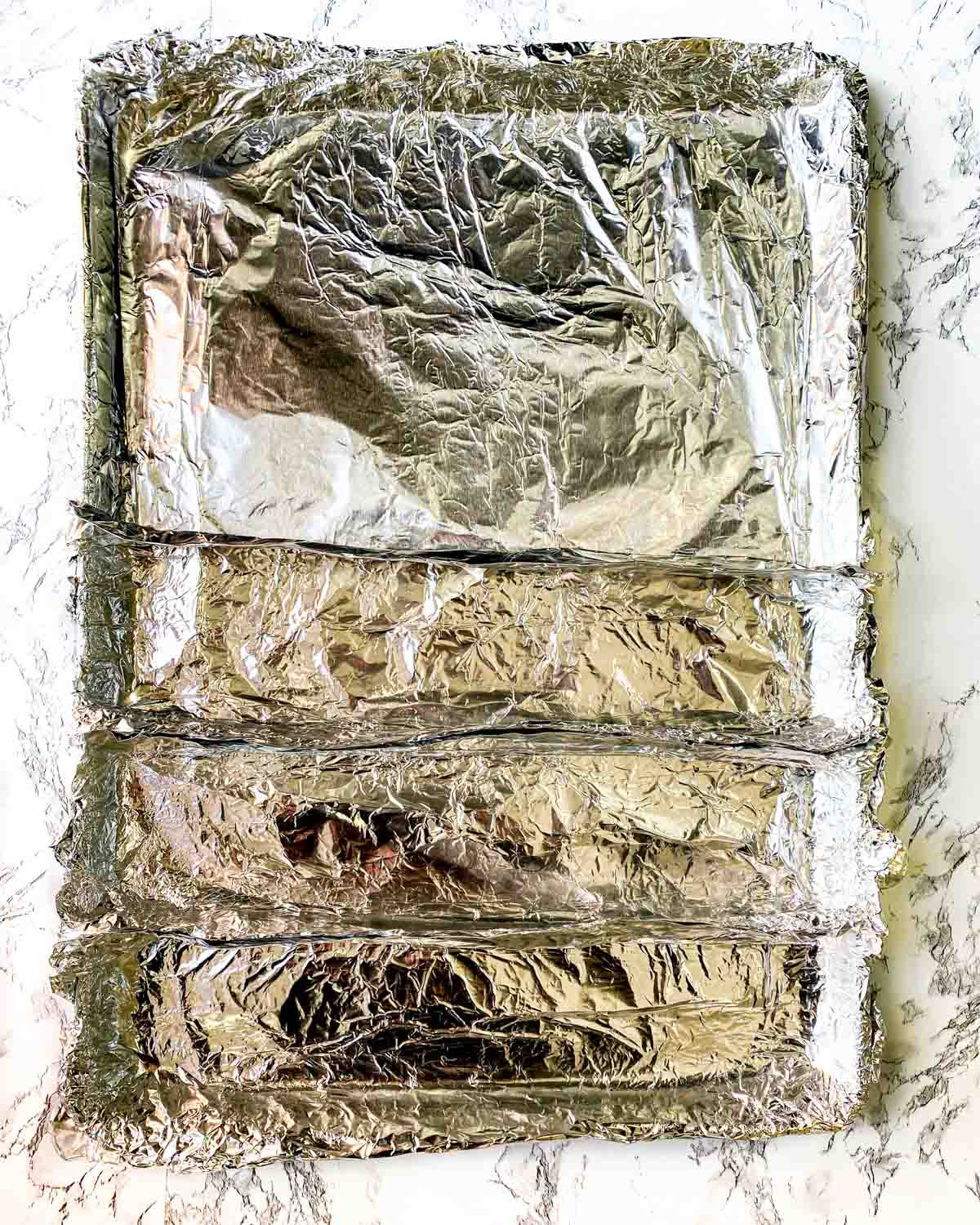 Sheetpan covered in foil, with additional foil sheets creating 4 total compartments.