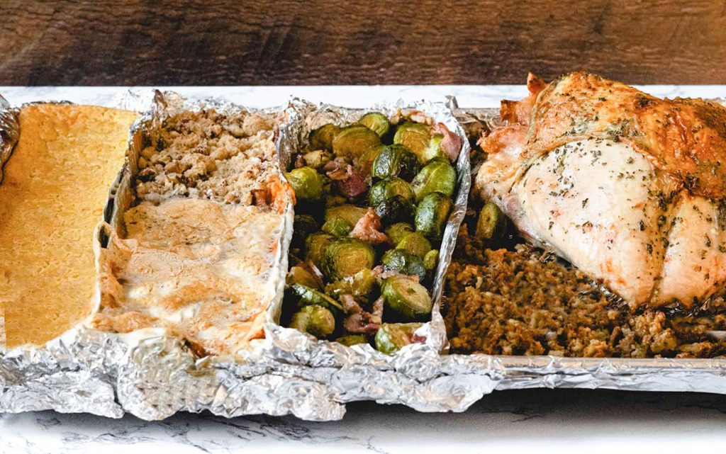 One sheetpan, divided with foil into 4 sections. Includes corn casserole, sweet potato casserole, Brussels sprouts, stuffing, and turkey.