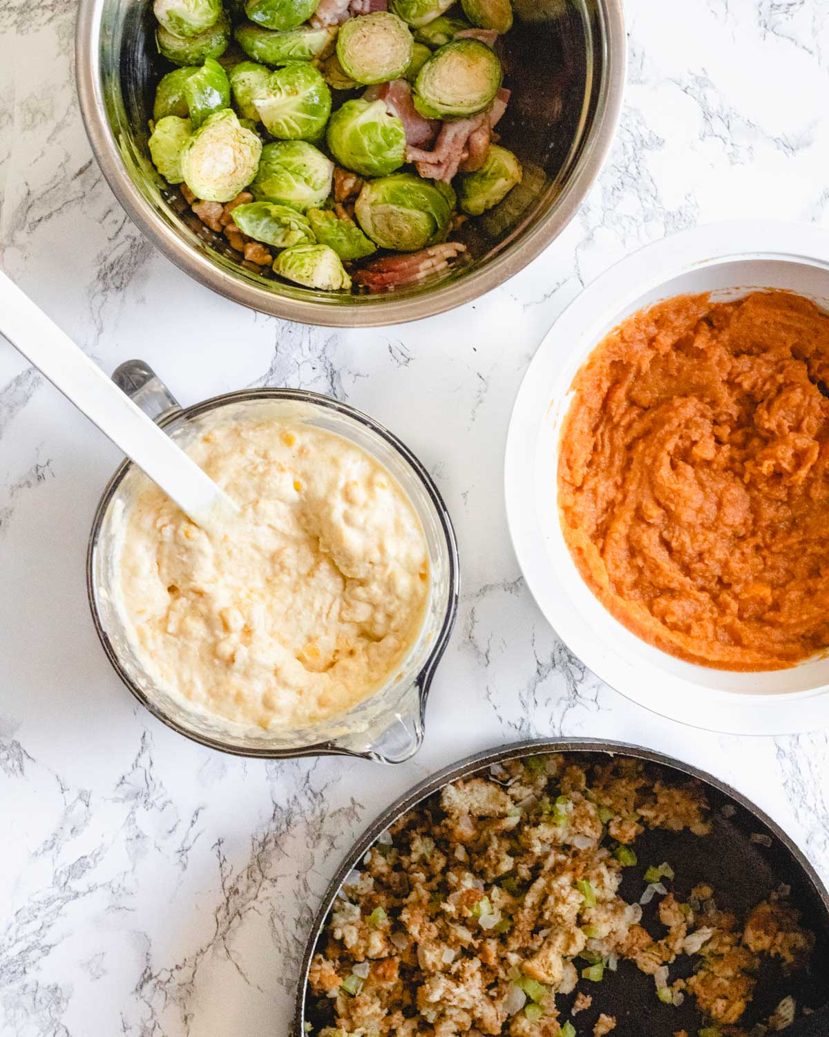 4 side dishes in separate bowls: Brussels sprouts, corn casserole, sweet potato casserole, and stuffing.