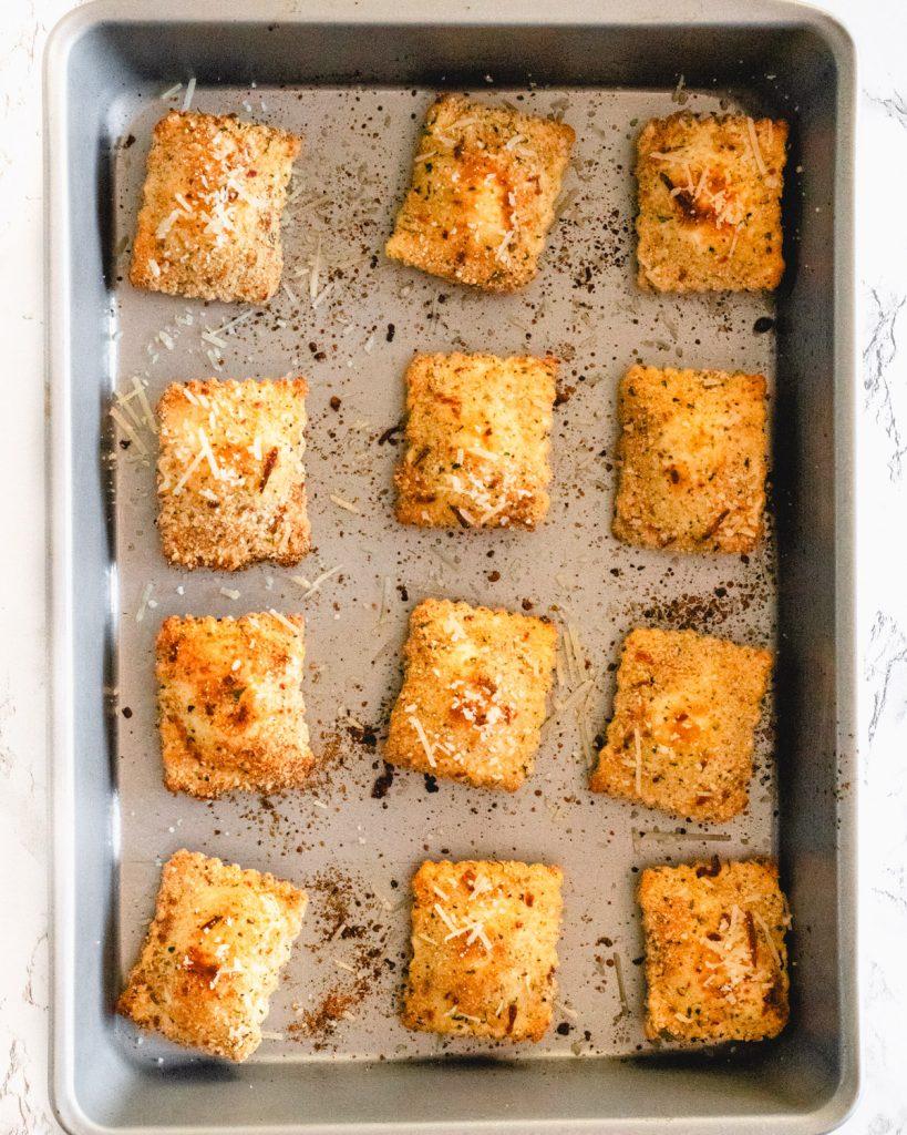Twelve pieces of toasted ravioli in a 9x13 pan.