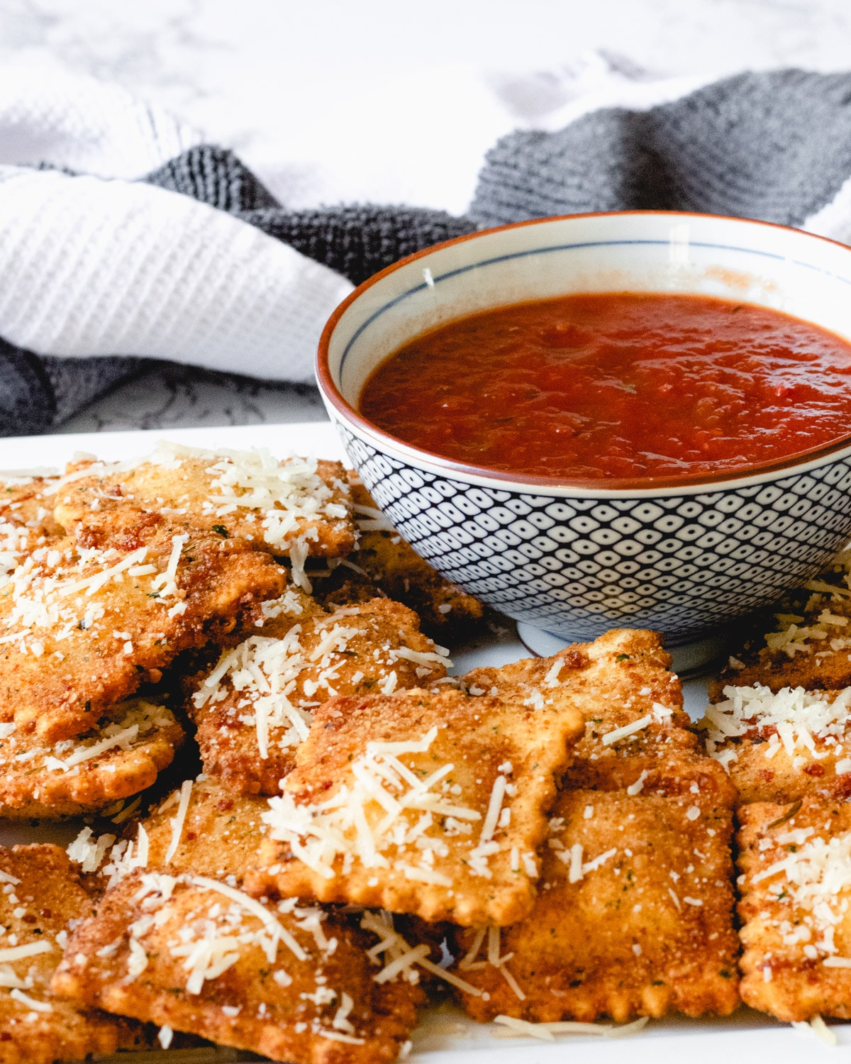 Plate of toasted ravioli that has been sprinkled with Parmesan cheese, and a bowl of marinara sauce.
