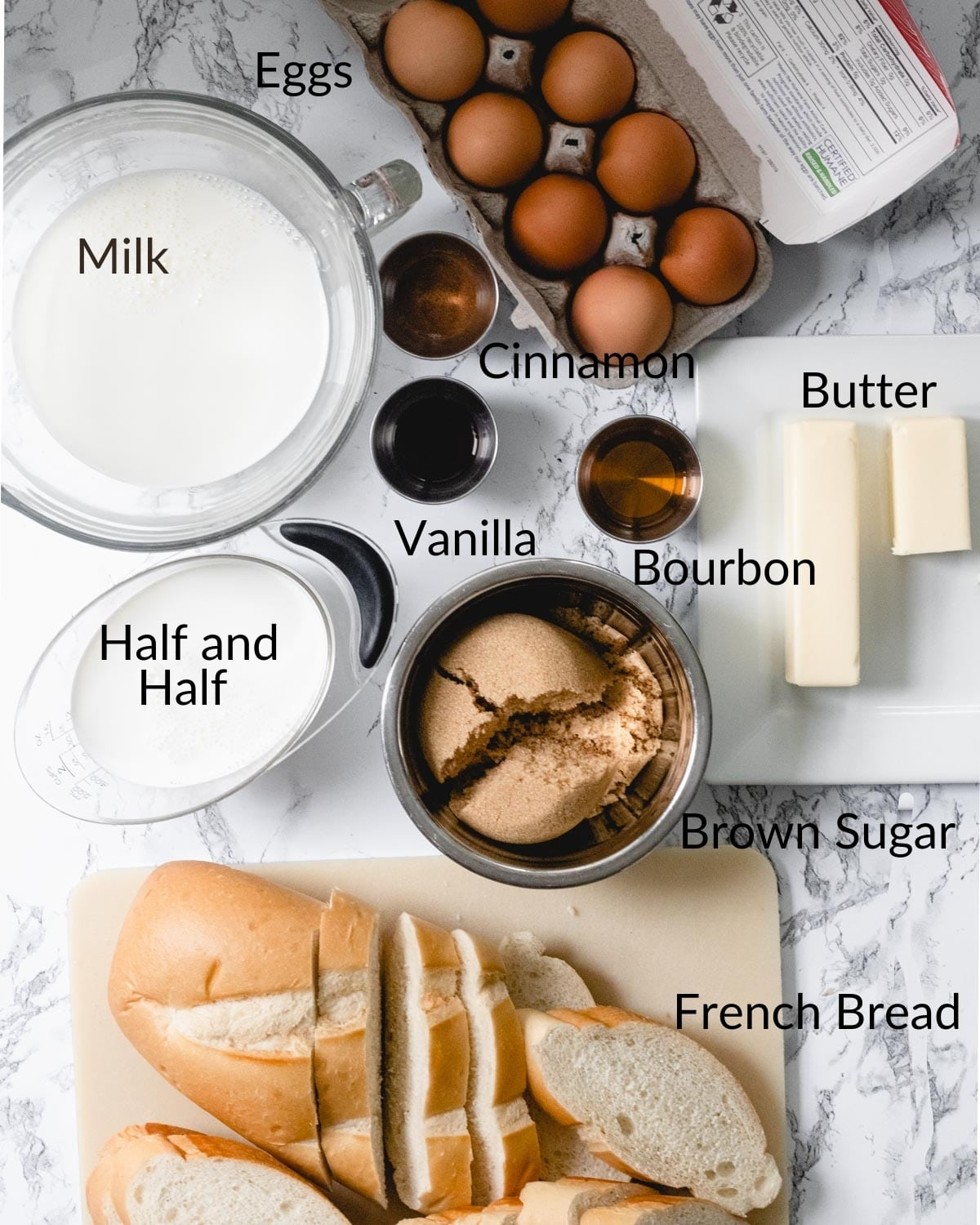 Ingredients for bourbon French toast casserole: milk, half and half, eggs, French bread, cinnamon, vanilla, bourbon, brown sugar, and butter.