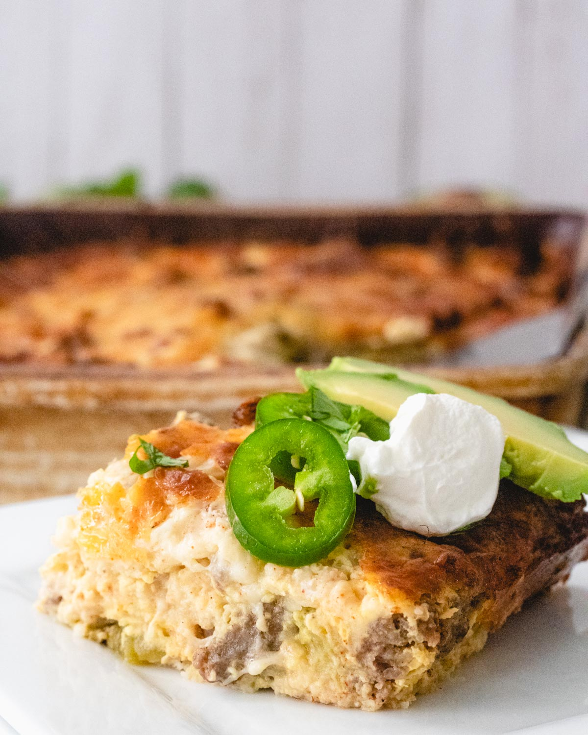 A slice of green chile breakfast casserole on a plate, topped with jalapeno, sour cream, and avocado, with the pan of casserole in the background.
