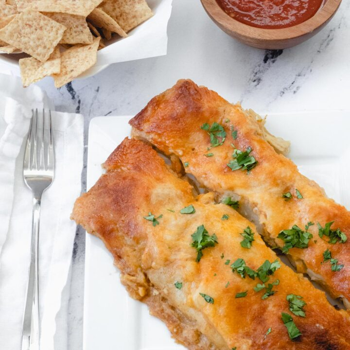 green chili enchiladas with chips and salsa.