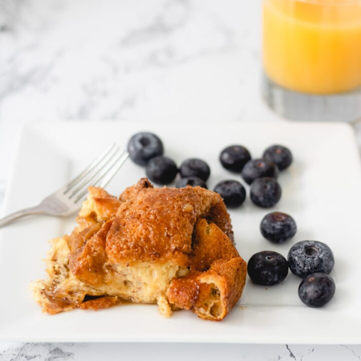 Plate of bourbon French toast with blueberries and a glass of juice.