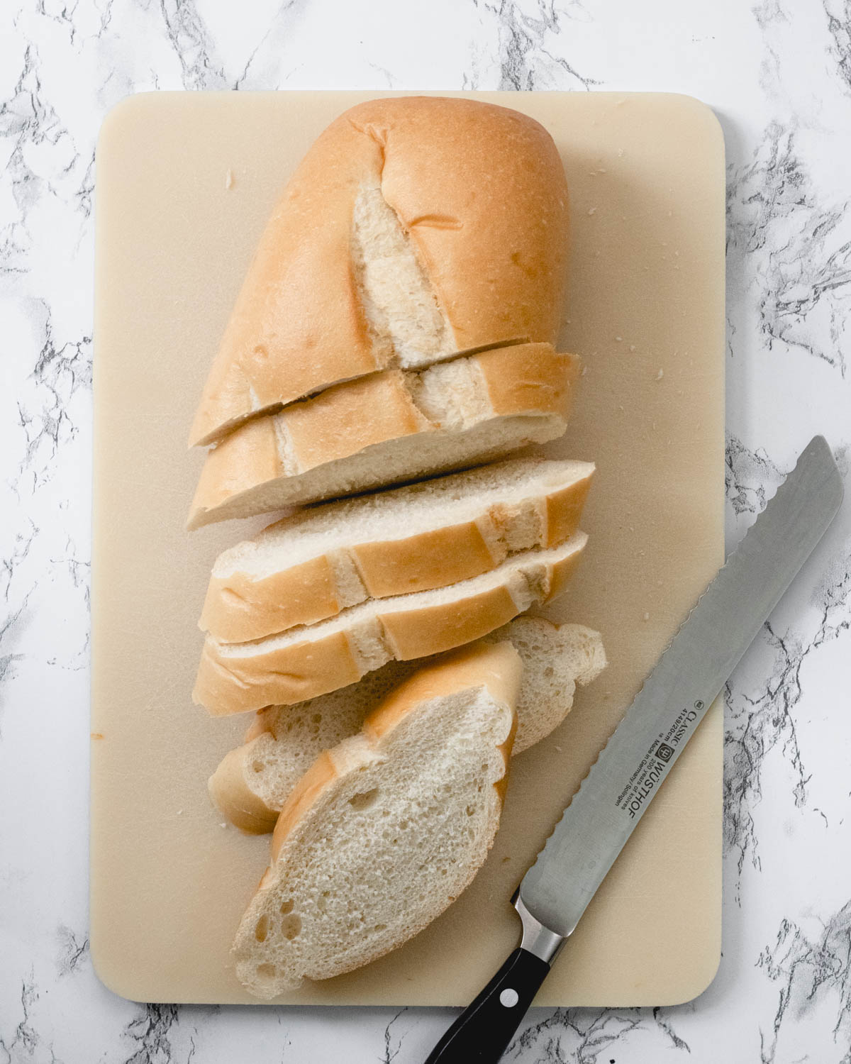 Sliced French bread on a cutting board with knife.