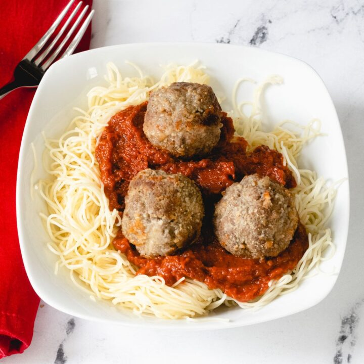 A square bowl of spaghetti topped with 3 meatballs.