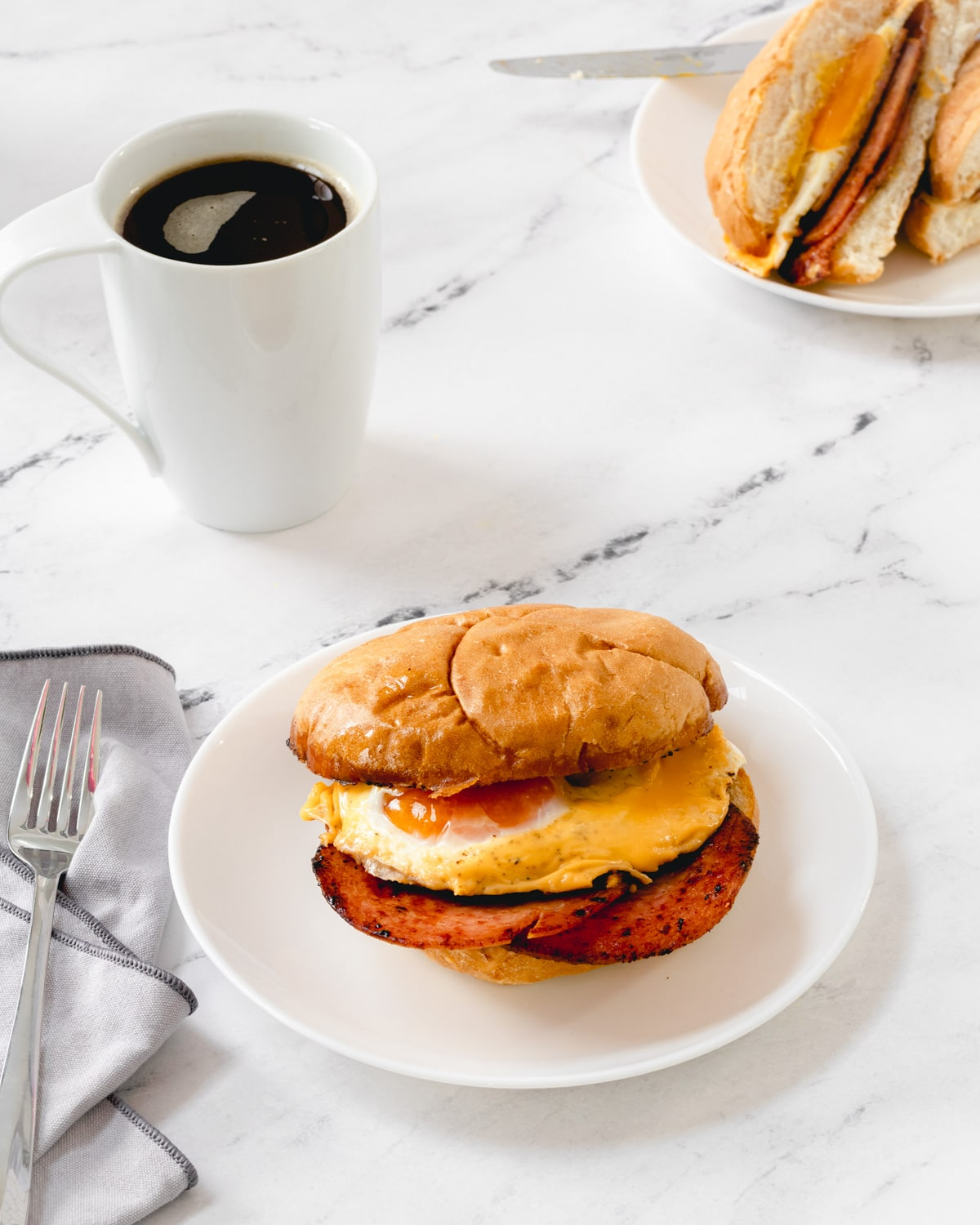 Pork roll egg and cheese sandwich on a white plate with a cup of coffee.