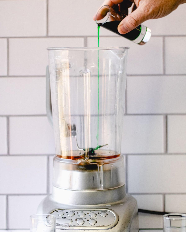 Pouring creme de menthe into the blender.