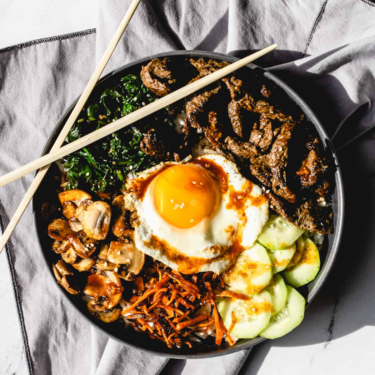 A bowl of bibimbap with chopsticks in the top left of bowl..