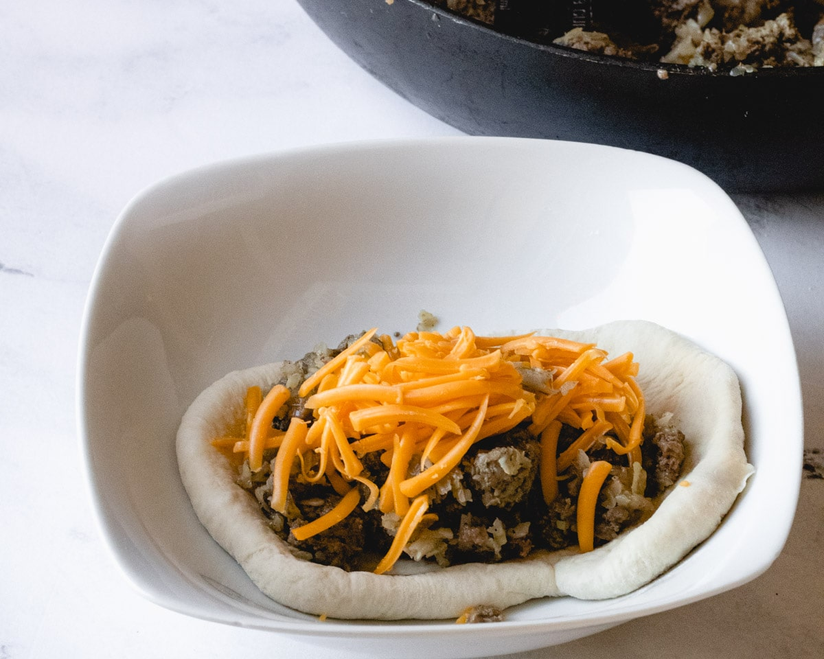 Bread dough in a bowl, topped with meat filling and shredded cheese.