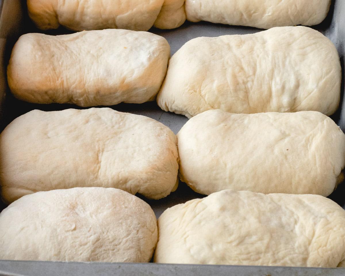 Bierocks rising side by side in a baking dish.