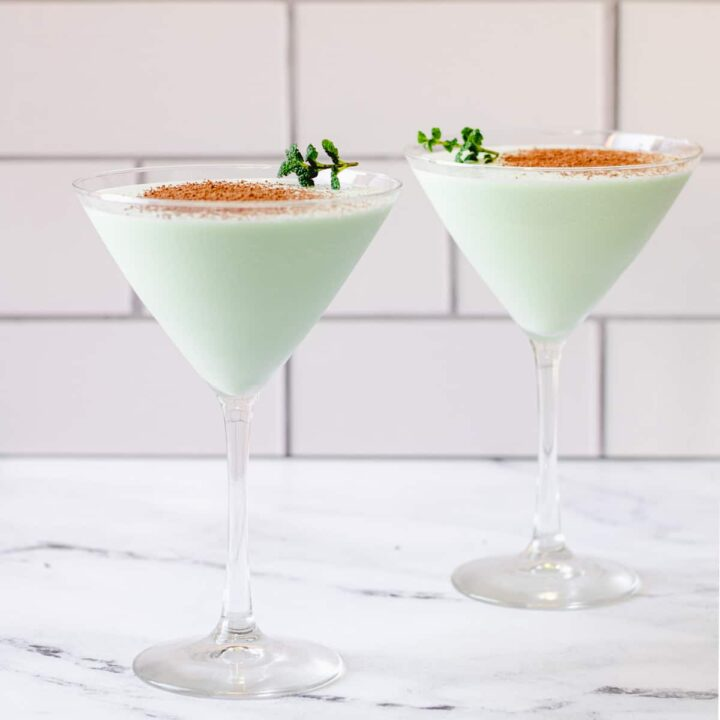 two glasses of brandy ice with cocoa powder and mint leaves.