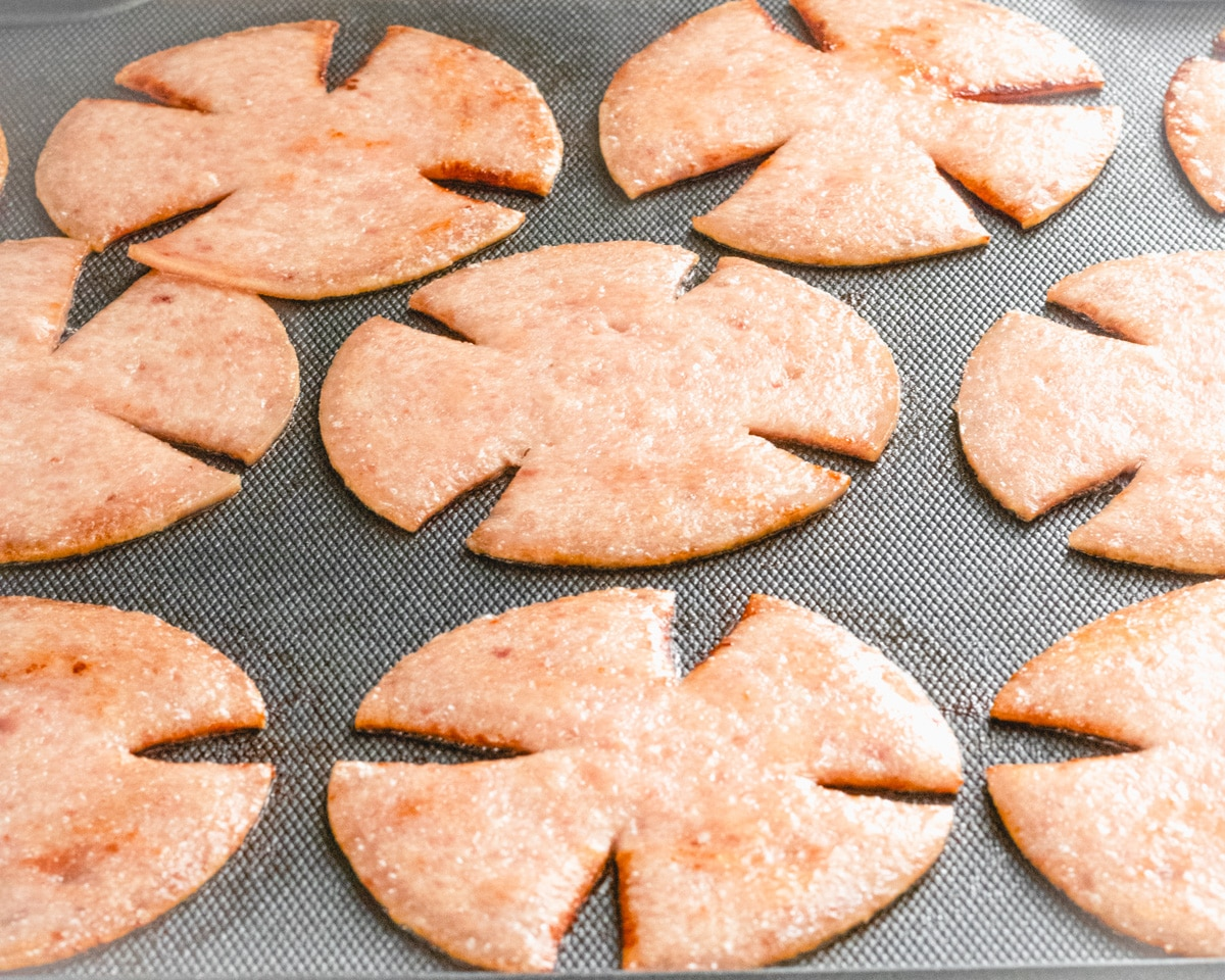 Grilling pork roll slices that have slashes in them, so they look like pinwheels.