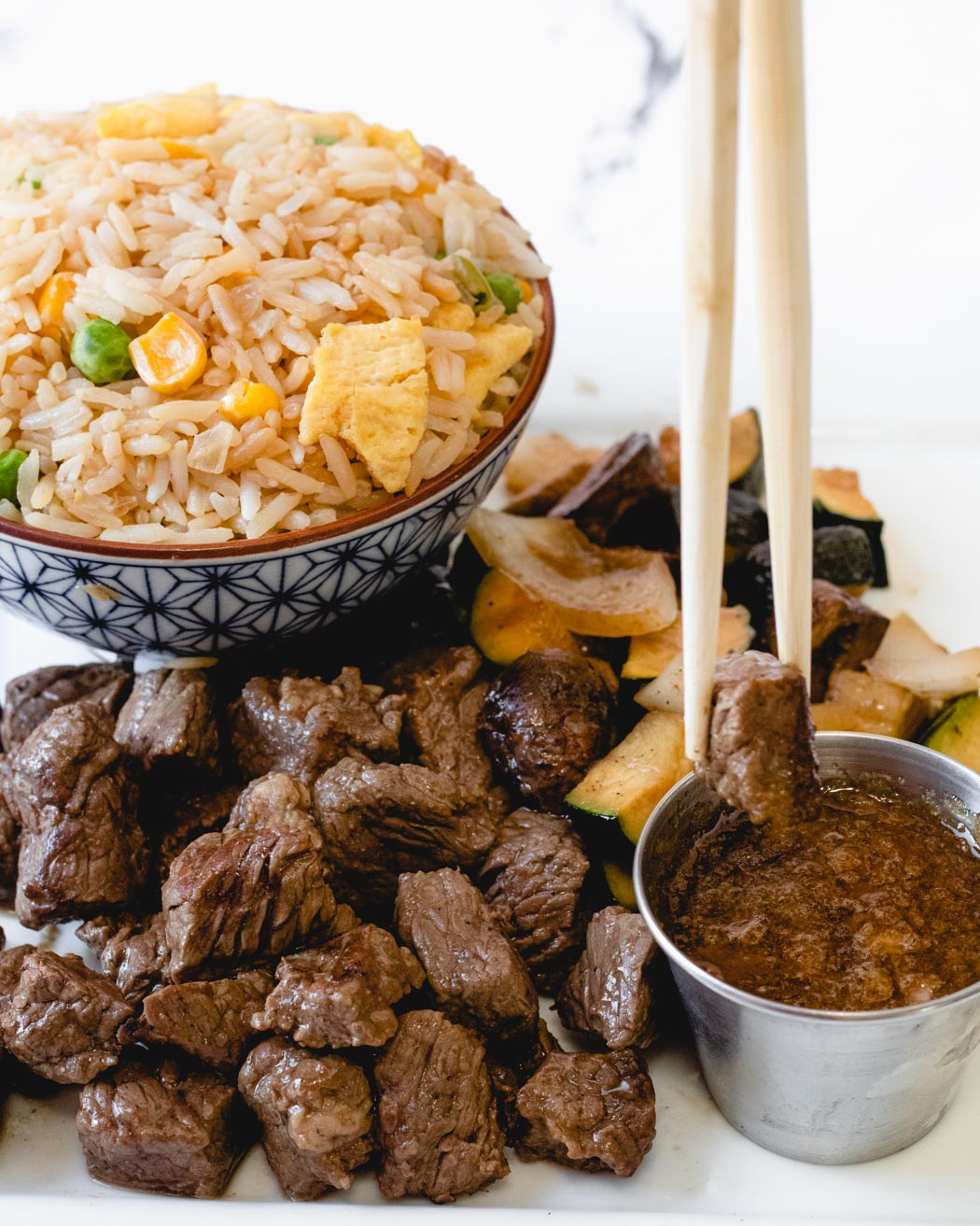 Plate of steak pieces, veggies, and fried rice with chop sticks dipping a piece of beef into ginger sauce.