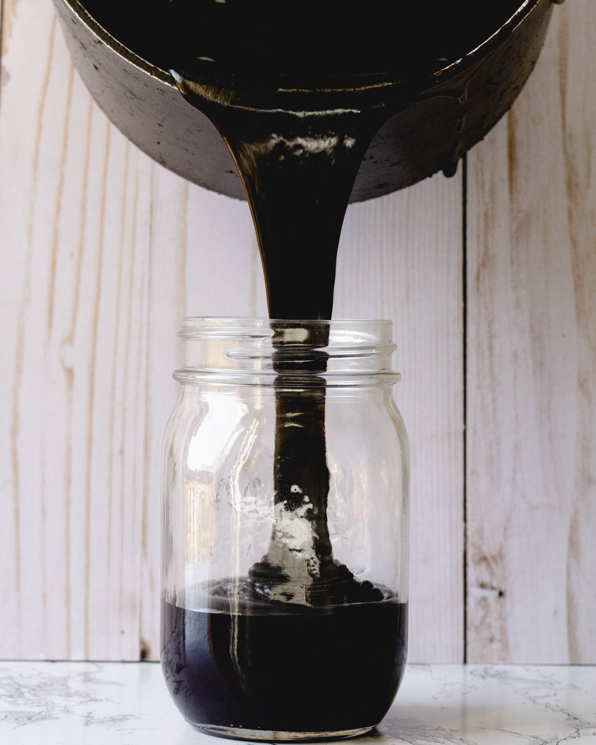 Pouring hot fudge into a mason jar.