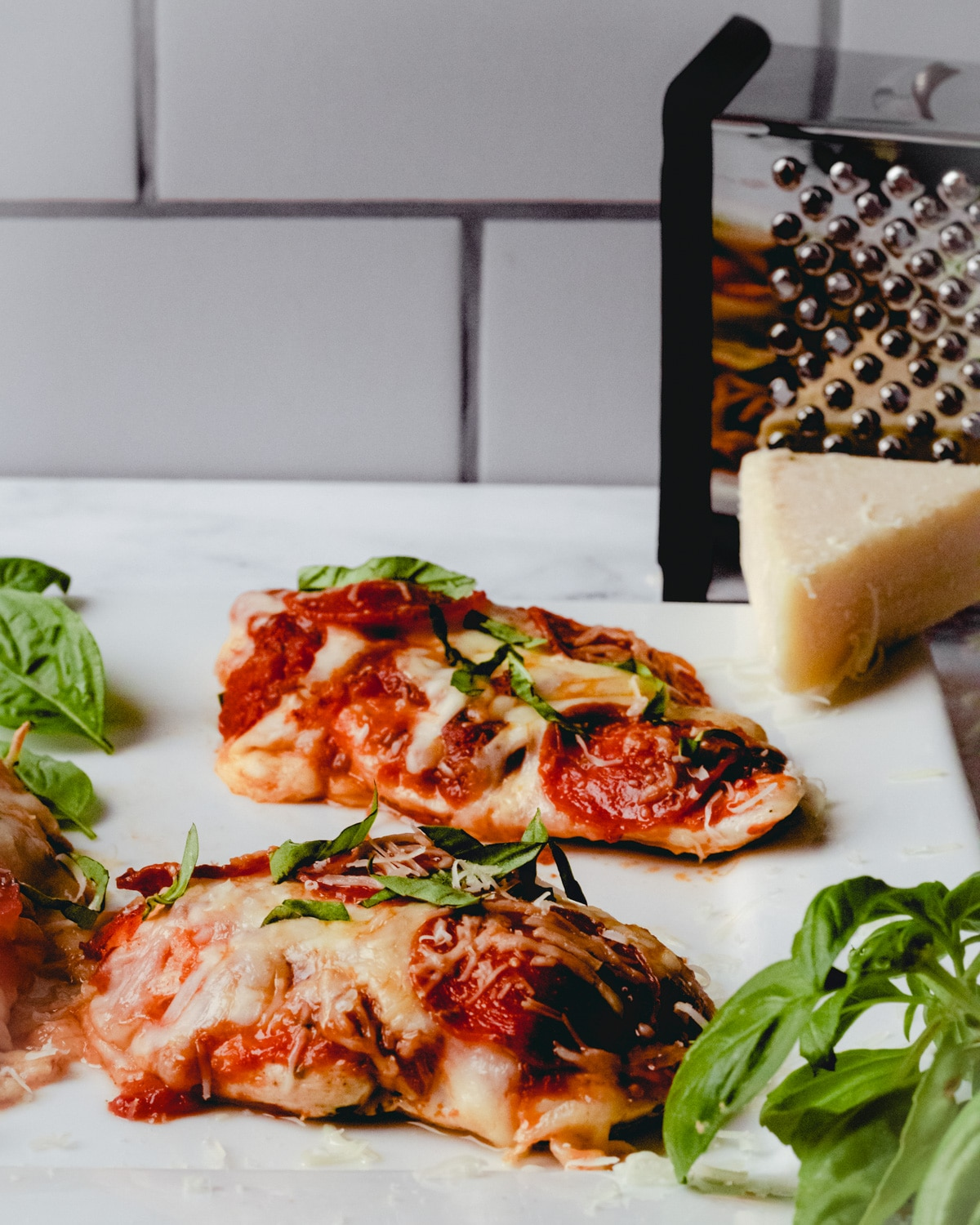 Two pieces of pizza chicken on a plate topped with basil, and a wedge of parmesan cheese in the corner.
