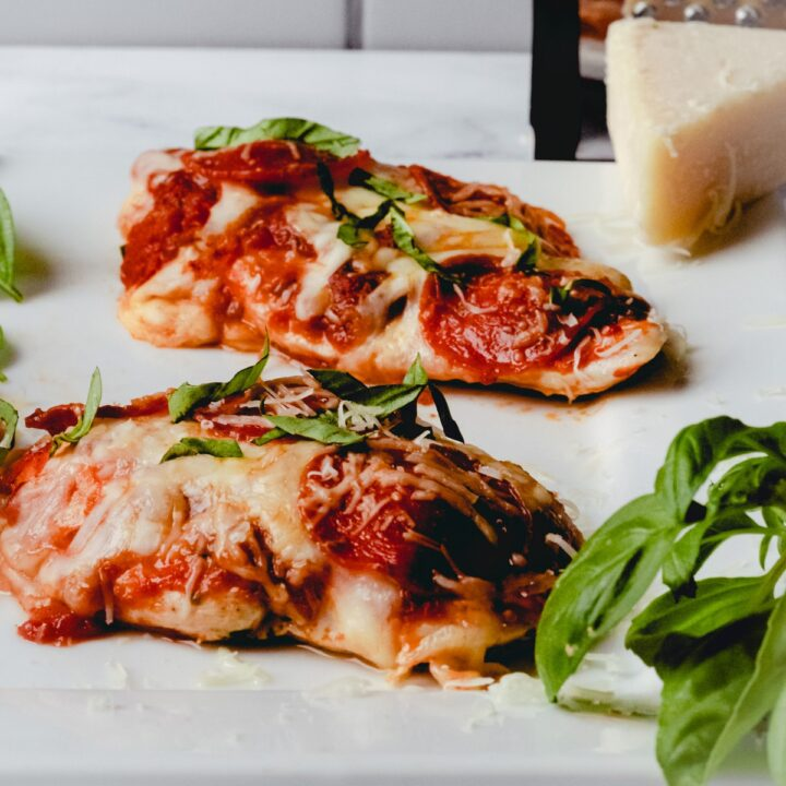 Two pieces of pizza chicken on a plate with some basil and a wedge of Parmesan.