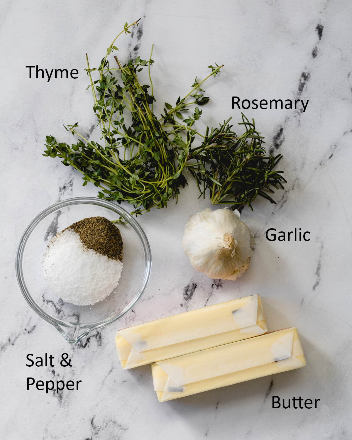 Garlic herb butter ingredients are pictured, including thyme, rosemary, garlic, salt, pepper, and butter.