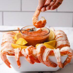 Shrimp hanging over the edge of a square bowl with cocktail sauce in the center and lemon wedges in between. Hand dipping one piece of shrimp into sauce.