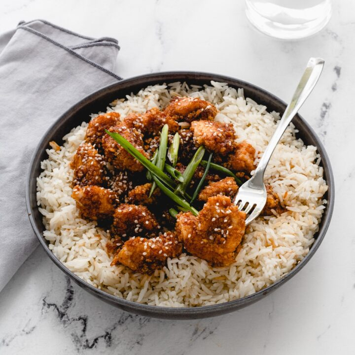 Bowl of sticky garlic chicken bites on rice, with a fork sticking into one bite.